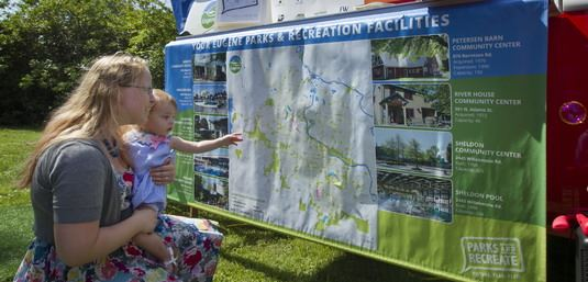 Mother and child looking at the Parks and Recreation System Map