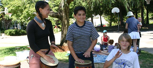 Three people drumming at a community neighborhood event