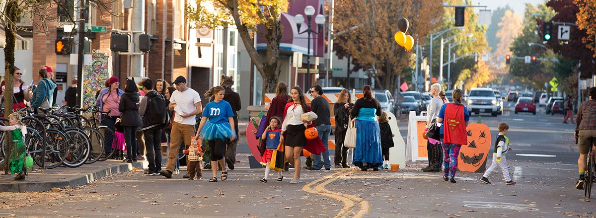 Families trick-or-treat downtown during annual All Hallow's Eugene event.
