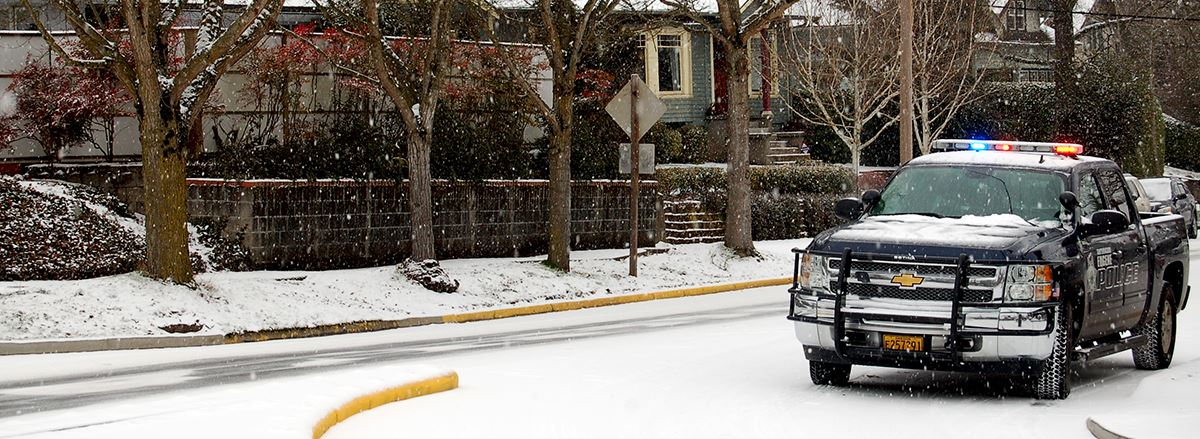 Eugene Police truck driving through a neighborhood on a snowy day