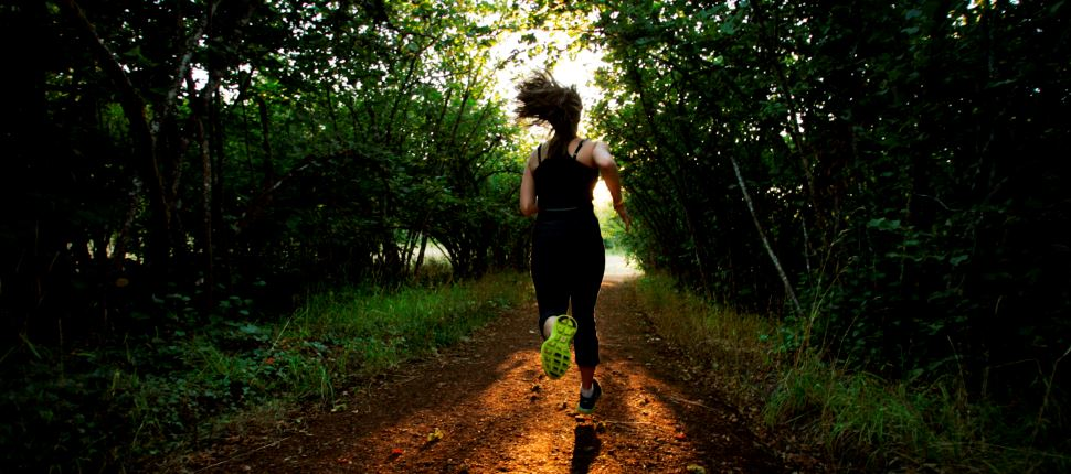 a woman running on pre's trail