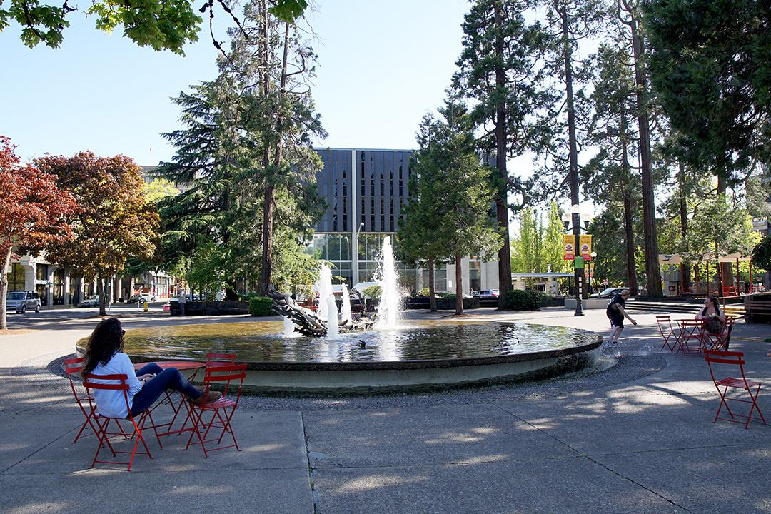 A person sitting at a table in front of a fountain at the Park Blocks in downtown Eugene