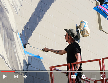 Artist painting a new mural as part of the 20x21 EUG Mural Project during Visual Arts Week 2019