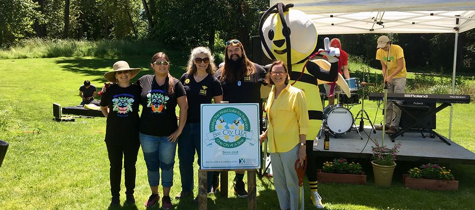 mayor vinis and group of people standing behind Bee City USA sign