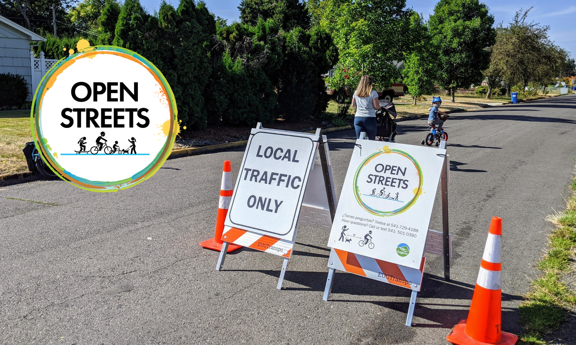 woman with baby carriage and young boy on a bike walking/rolling by the Open Streets sign