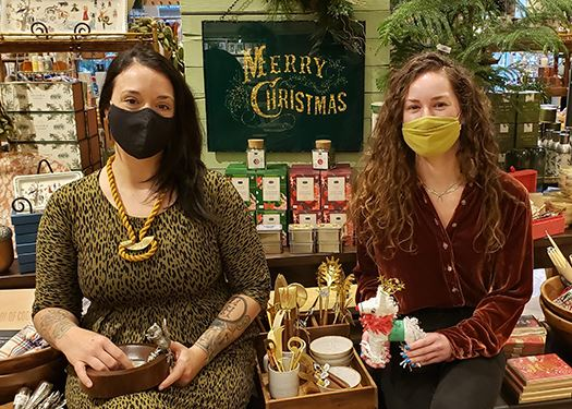 Two Passionflower employees wearing masks showing off merchandise ahead of Small Business Saturday.