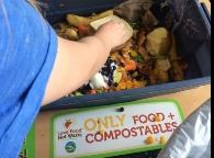 Elementary students collecting food waste in a cafeteria for composting
