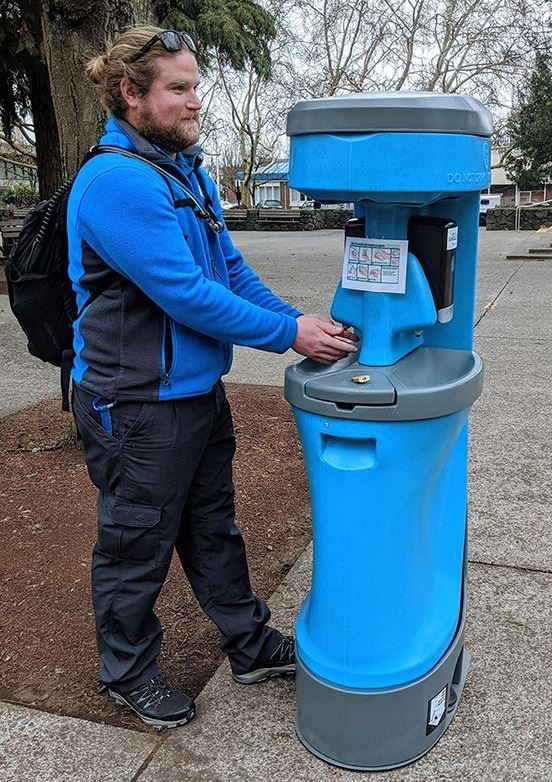 Downtown Ambassador using a new public handwashing station in the Park Blocks, installed to help pre