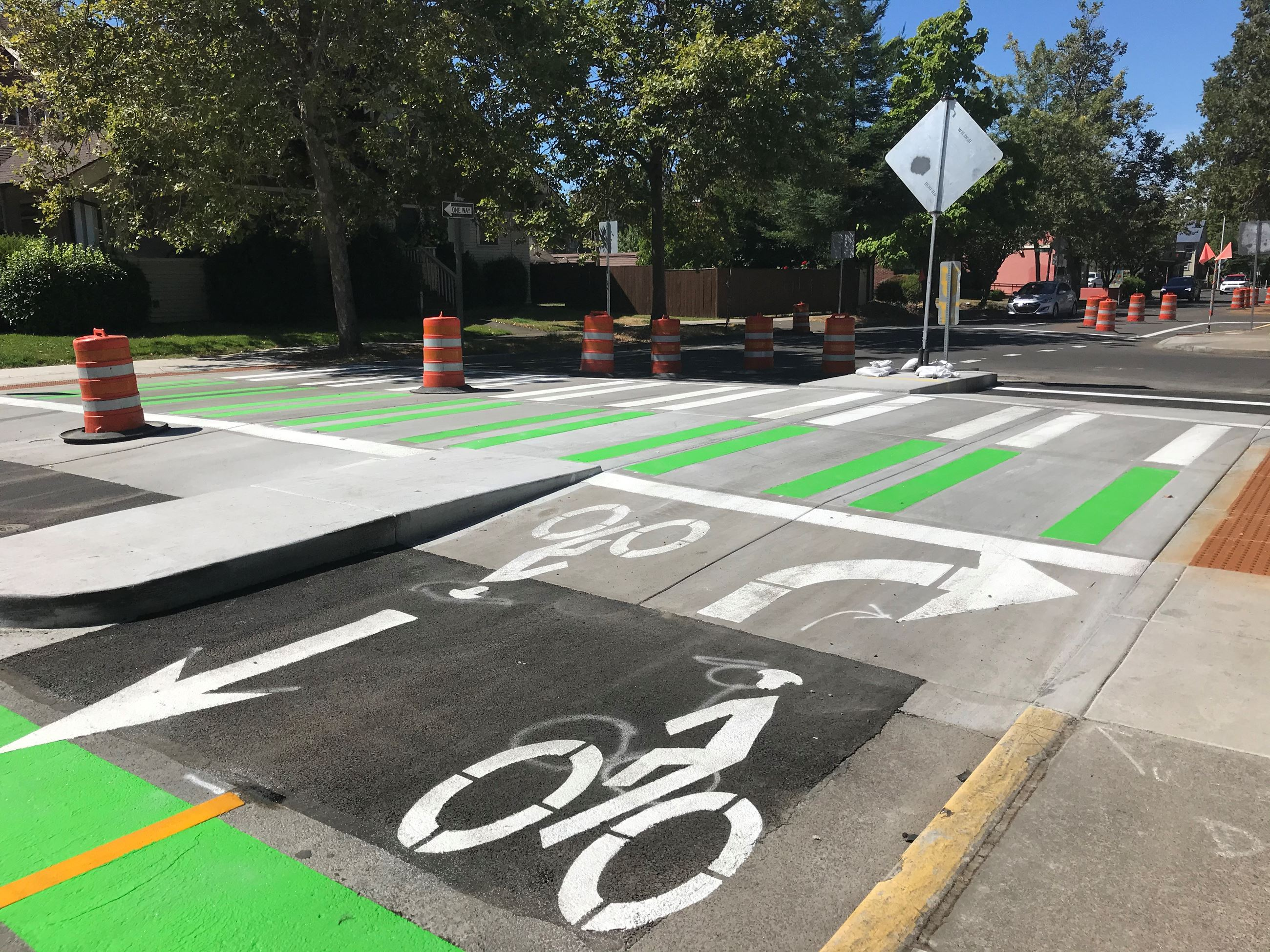 13th Avenue Bikeway at 13th and Lawrence. Green painted two-way protected bike lanes.