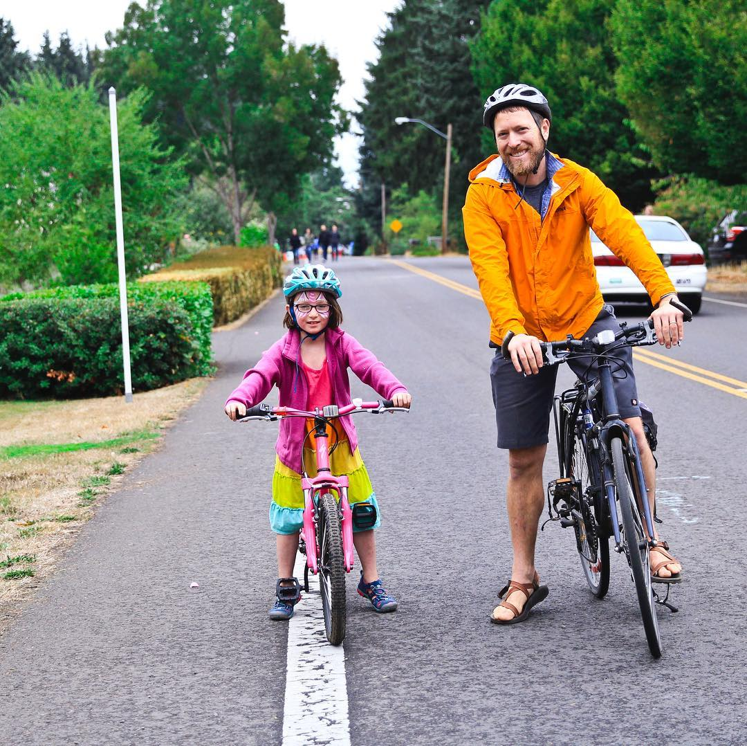 Father and daughter pose for photo on their bikes