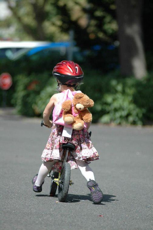 Child Biking with Teddy Bear