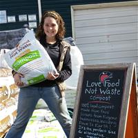 Photo of Down To Earth employee holding bag of Love Food Not Waste compost.